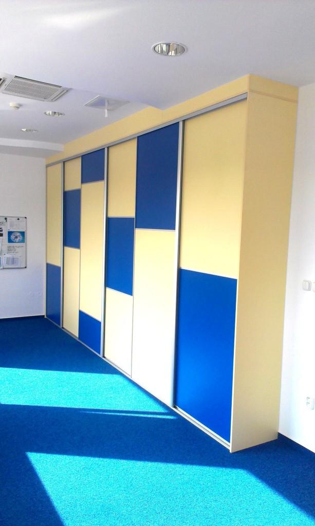 Vstavaná skriňa do kancelárie, Košice, materiál: korpus, DTD sivá, dvere: modrá- žltá 18mm, predel hliníkovým profilom, kovanie: hliník, konzoly: nerez, vnútorné riešenie: police na odkladanie krabíc, vešanie na vetrovky, posuvné dvere